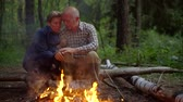 compromisso : Happy elderly couple sitting together by the fire on the nature Vídeos