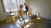 strengthen : Fitness instructor explaining leg exercise on a reformer to client.