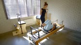 resistência : Beautiful woman working with instructor in pilates class. Stock Footage