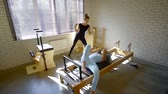 strengthen : Professional fitness trainer helps woman with exercise on a reformer in studio. Stock Footage