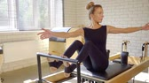 strengthen : Sporty woman stretching her upper body using reformer in pilates class.