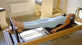 strengthen : Athletic girl in blue sportswear pushing on a resistance pilates machine - reformer.
