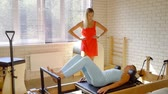 strengthen : Professional pilates trainer training woman indoor. Stock Footage