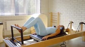 strengthen : Side view shot of a fitness girls doing leg exercise on a reformer. Stock Footage