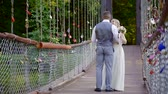 гетеросексуальные пары : young bride and groom are dancing on suspension bridge, romantic first dance of honeymooners