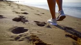 沿岸の : close-up of woman foot in sneakers walking along the sea on a sandy beach early in the morning on vacation