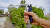 hosepipe : Close-up shot of a womans hand with a hose watering lawn, water under pressure.