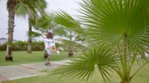 後退 : Shooting of a happy married couple enjoying walk on a resort, palm trees and hot weather. 動画素材