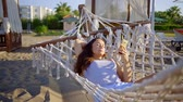 hamak : Lovely brunette woman relaxing in a hammock on a beach, checking social media on smartphone.