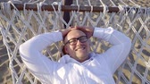 broadly : cheerful bald man is relaxing in a white beach hammock in seashore and smiling broadly