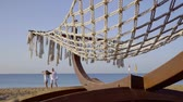 spouses : happy pair is dancing on a sea coast in morning, straps hammock is swaying by wind