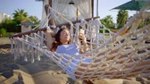 hamak : relaxed woman is resting in a wicker hammock in sand beach in summer morning, using smartphone
