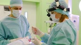 dokular : woman surgeon and her male assistant are working over nose and nasal septum of patient