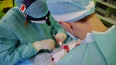 dokular : cosmetic surgeons are performing operation on nasal partition, main doctor and his assistant