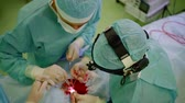 dokular : top view of working surgeons and patient lying on table, during rhinoplasty operation