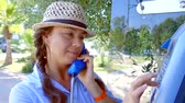 discagem : cheerful adult woman is taking handset of public phone outdoors in sunny day, dialing number