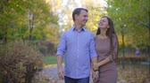 beslemek : Married couple taking a stroll in a park in autumn, happy relationship. Stok Video