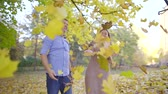 cherish : Happy joyful couple throwing yellow and red leaves in the air in park in fall.