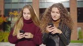enviar : two female schoolmates are strolling in school yard in break time in autumn sunny day, using smartphones Vídeos