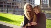 camarada : pair of young students girls is sitting on grass in city park, looking on mobile phone screen Stock Footage