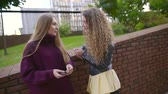 beca : two young sisters is gossiping, chatting and laughing outdoors in fall day, speaking joke