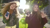 camarada : two young women are dancing on open air party in city park in sunny autumn day, holding phones Stock Footage