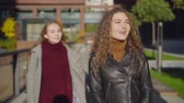 camarada : student girl is waitng her friend on a street, other girl is approaching from back and hugging her Stock Footage