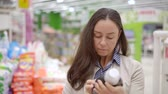 cárpatos : adult cute woman reads the label on the detergent while standing in the supermarket