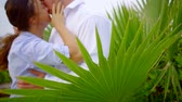 retiro : beautiful affectionate couple kissing by the palm leaves, love on vacation.