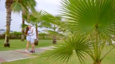 後退 : Cute married couple taking a walk on resort in distance, palm trees and hot weather.