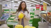 agd : brunette woman is checking melon in hall of food supermarket, touching fruits and sniffing
