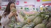 cheirando : adult female shopper is sniffing and touching pineapples in a store, choosing fruits for family Vídeos