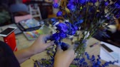 ručně malovaná : close-up of the hand of the master of decorating. collects a bouquet of flowers painted in blue Dostupné videozáznamy
