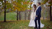 жена : happy bride with her groom is walking in autumn park in their wedding day, strolling along lake