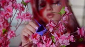 азиатский : young woman is installing origami figure on branch of sakura with pink flowers, close-up of hand