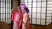 gueixa : Two beautiful girls dressed as anime charachters, pink kimonos and lovely bright wigs and bunny ears.