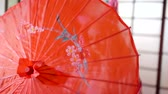 maiko : Girl hiding behind red japanese umbrella indoor. Stock Footage