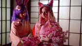 maiko : Two beautiful anime girls with pink and purple wigs wearing pink and holding sakura branches.