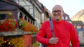 half timbered : middle aged bald man with glasses is laughing good, changing face expression from skepticism