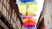 napernyő : bright multicolored umbrellas are hanging over city streets in small town, tilt up view