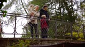 cheerfully : parents and preschoolers children are walking in botanical garden in autumn day, standing on bridge