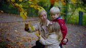 desenvolver : mother is showing to her preschooler son and girl a yellowed leaves in autumn day