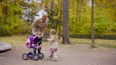 baby carriage : charming female child is approaching to her mom and kissing her, walking in park in autumn day