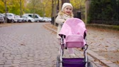 road : little girl is rolling a small toy pram on street in autumn day, playing happily