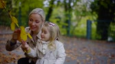 Close up shot of a blonde mother and little daughter looking closely at yellow leaf on a tree.