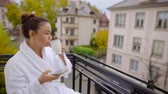 Portrait of a brunette woman with a cup of coffee and smartphone on balcony wearing white robe.