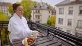 Beautiful middle-aged woman enjoying morning on the balcony with breakfast and smartphone. Stok Video