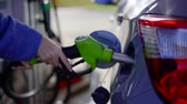 tankowanie : Close-up shot of a mans hand putting fuel nozzle in cars fuel tank. Wideo