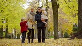 Father mother and two children enjoying lovely family walk in autumn park. Stok Video