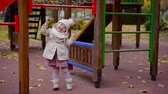 subida : Joyful smiling child enjoying day playing on a playground in autumn.